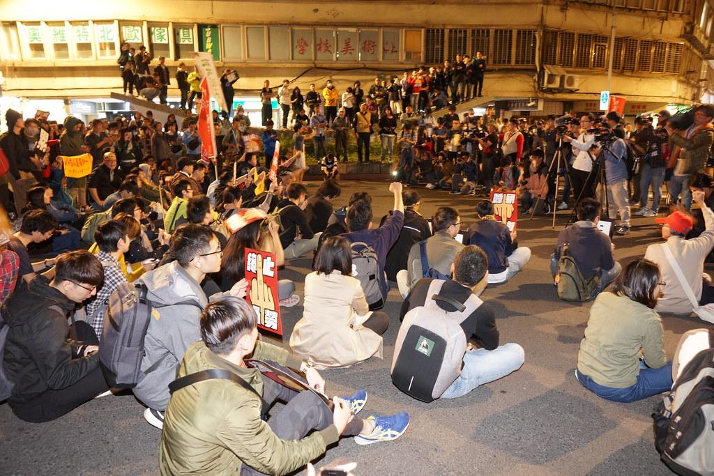 兩三百個群眾在遊行指揮宣布解散後仍持續佔據在行政院路口。(攝影:王顥中)