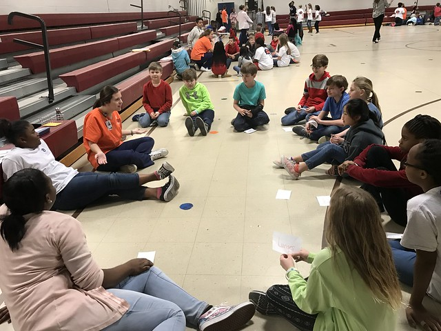 group of elementary school children sit in a circle with an Auburn University nursing student.