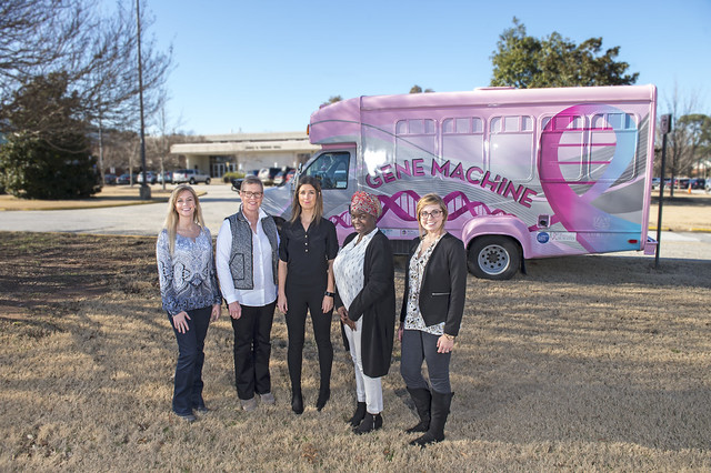 Five people stand in front of a short, pink bus with 'Gene Machine' on the side of it.