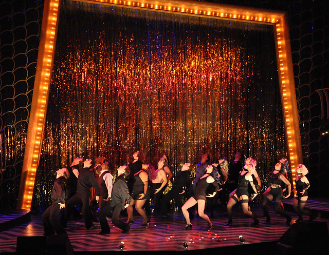 "A photo shows the full stage set up of ""Chicago"" with a metallic curtain backdrop and cast members dancing on stage."