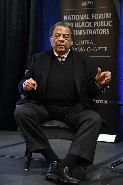 Civil rights activist Andrew Young sits on stage and speaks during the MLK Scholarship Breakfast