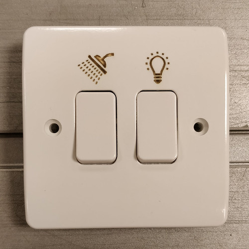 [White 2 gang light switch with a shower symbol engraved above the left switch and a light bulb engraved above the right switch]