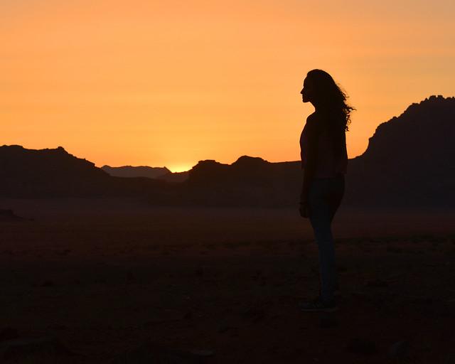 Contraluces en Wadi Rum a medida que el sol torna a dorado el cielo