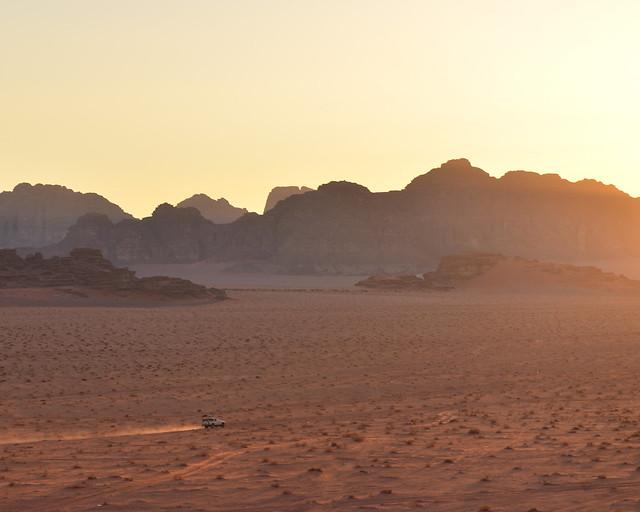 Un 4x4 a toda velocidad por el valle de Wadi Rum mientras el sol cae lentamente