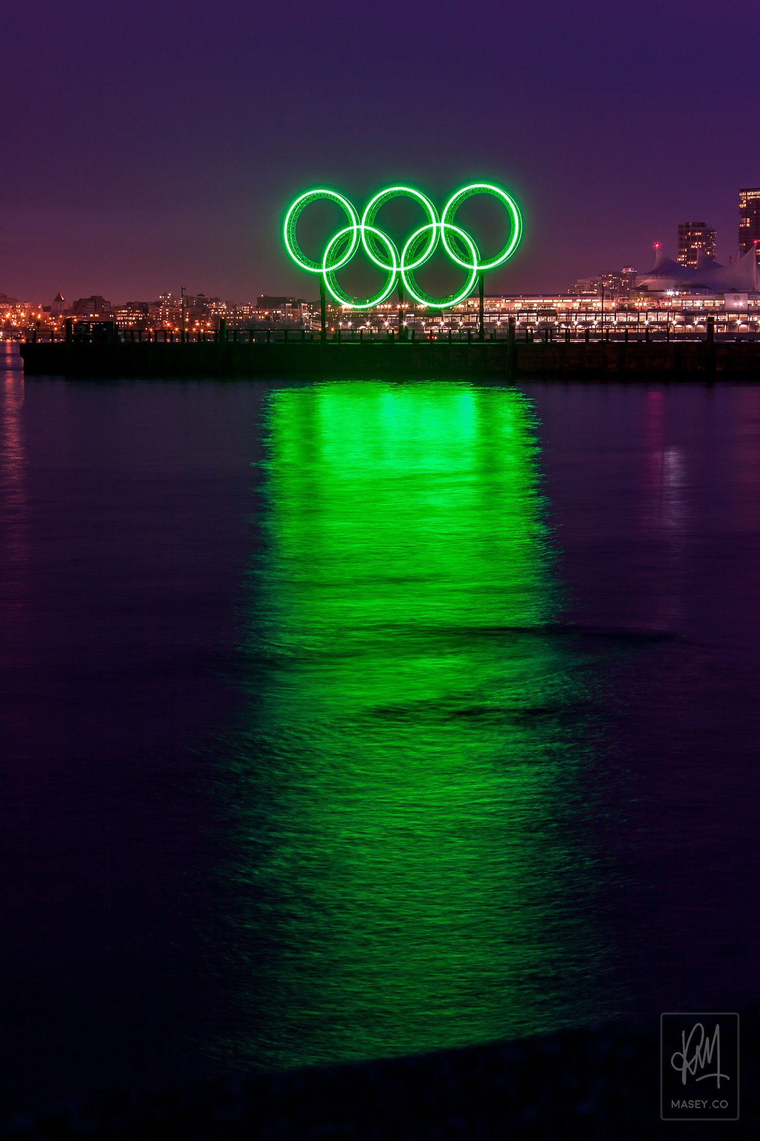 The Olympic rings shining brightly on the water in front of the Vancouver skyline.