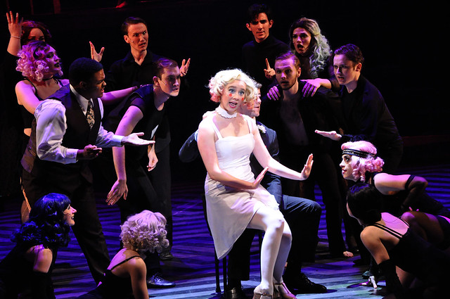 "A woman sits in a chair on stage and sings while other cast members look on during a dress rehearsal performance of ""Chicago."""