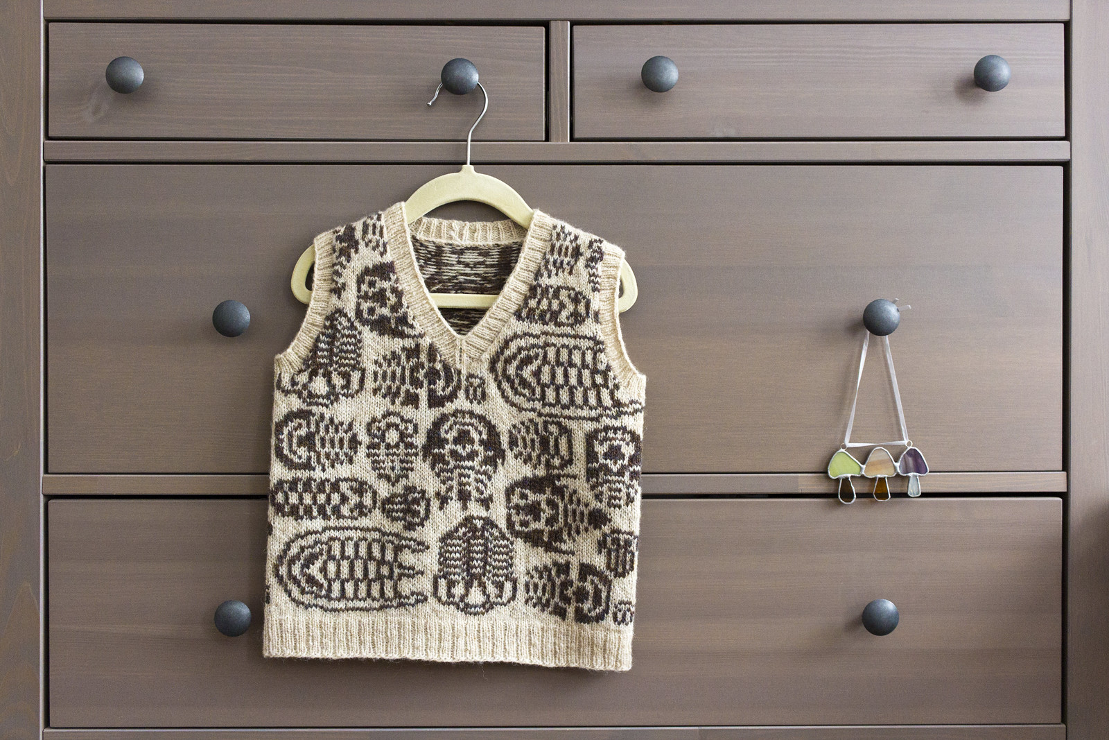 trilobite sweater vest hanging on a chest of drawers