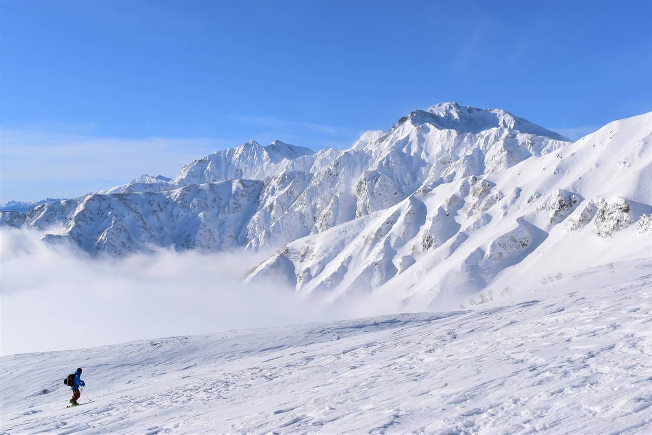 雪の五竜岳と鹿島槍ヶ岳と登山者