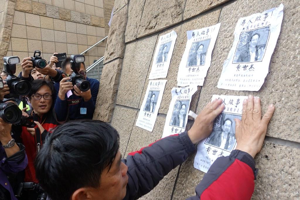 美麗華工人將「協尋黃世杰」的傳單貼在百貨外牆上。(攝影:張智琦)
