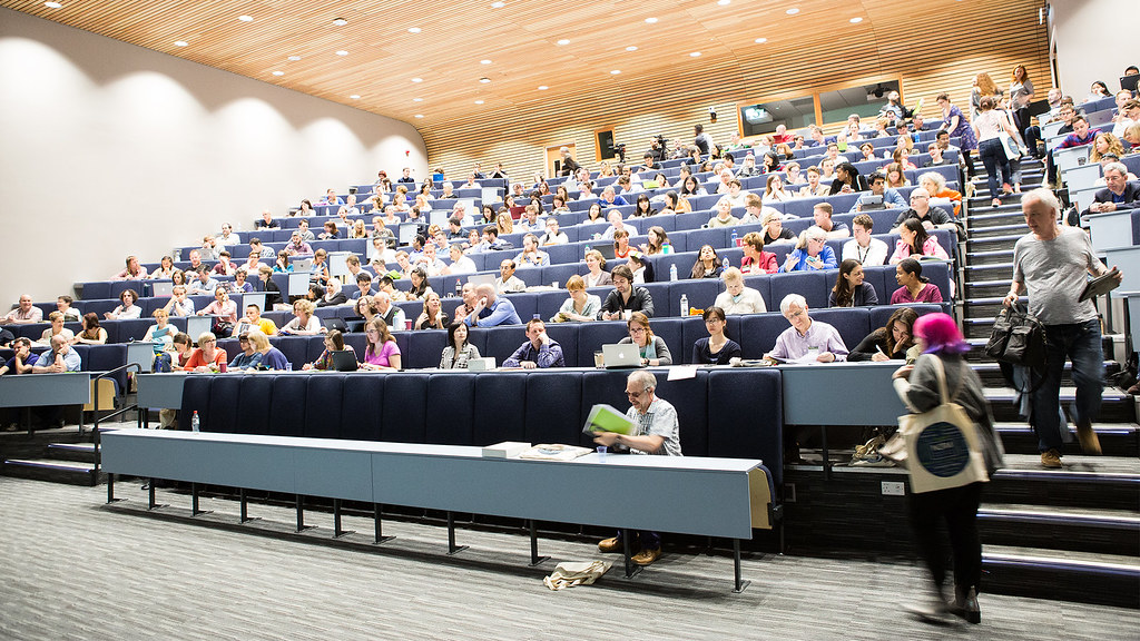 Tiered lecture theatre with students seated and walking through