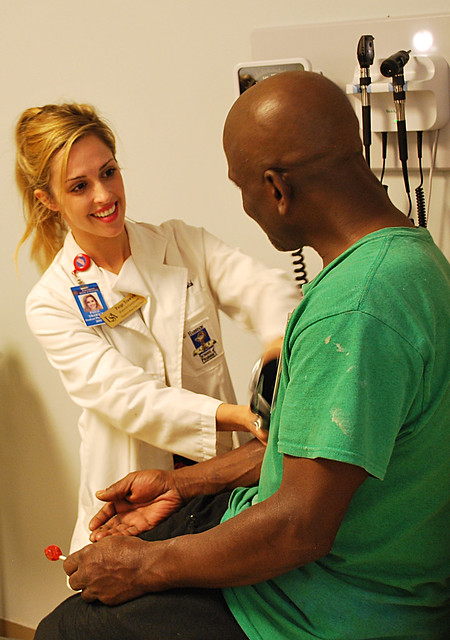 Auburn pharmacy student checks a patient's blood pressure in an exam room.