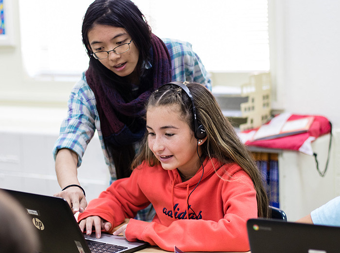 Heather Huynh, a researcher with the High Performance Computing Division at the Laboratory, works with a student during an Hour of Code session at Mountain Elementary in Los Alamos.