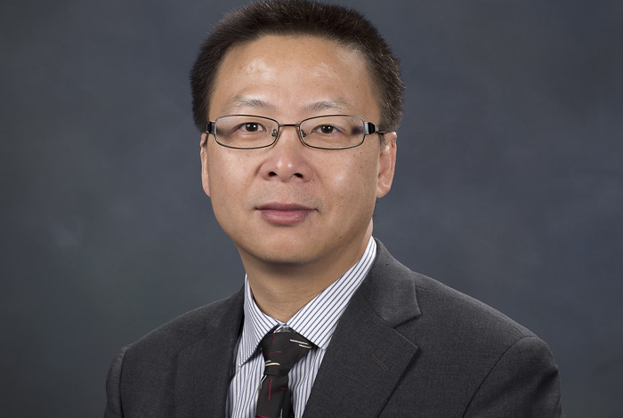 Portrait of Hou-Tong Chen wearing a black suit jacket and tie, with a black and white pinned strip shirt and wearing glasses