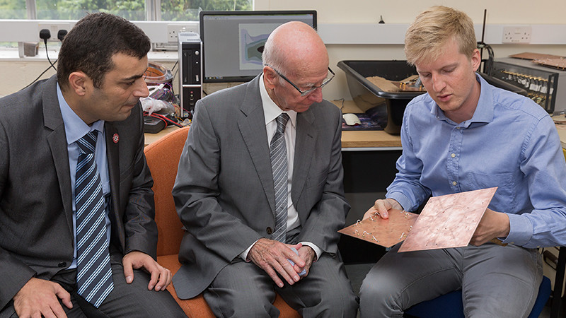 Sir Bobby Charlton talks with Dr Soleimani and PhD student Carl Chittenden about their research on landmine detection