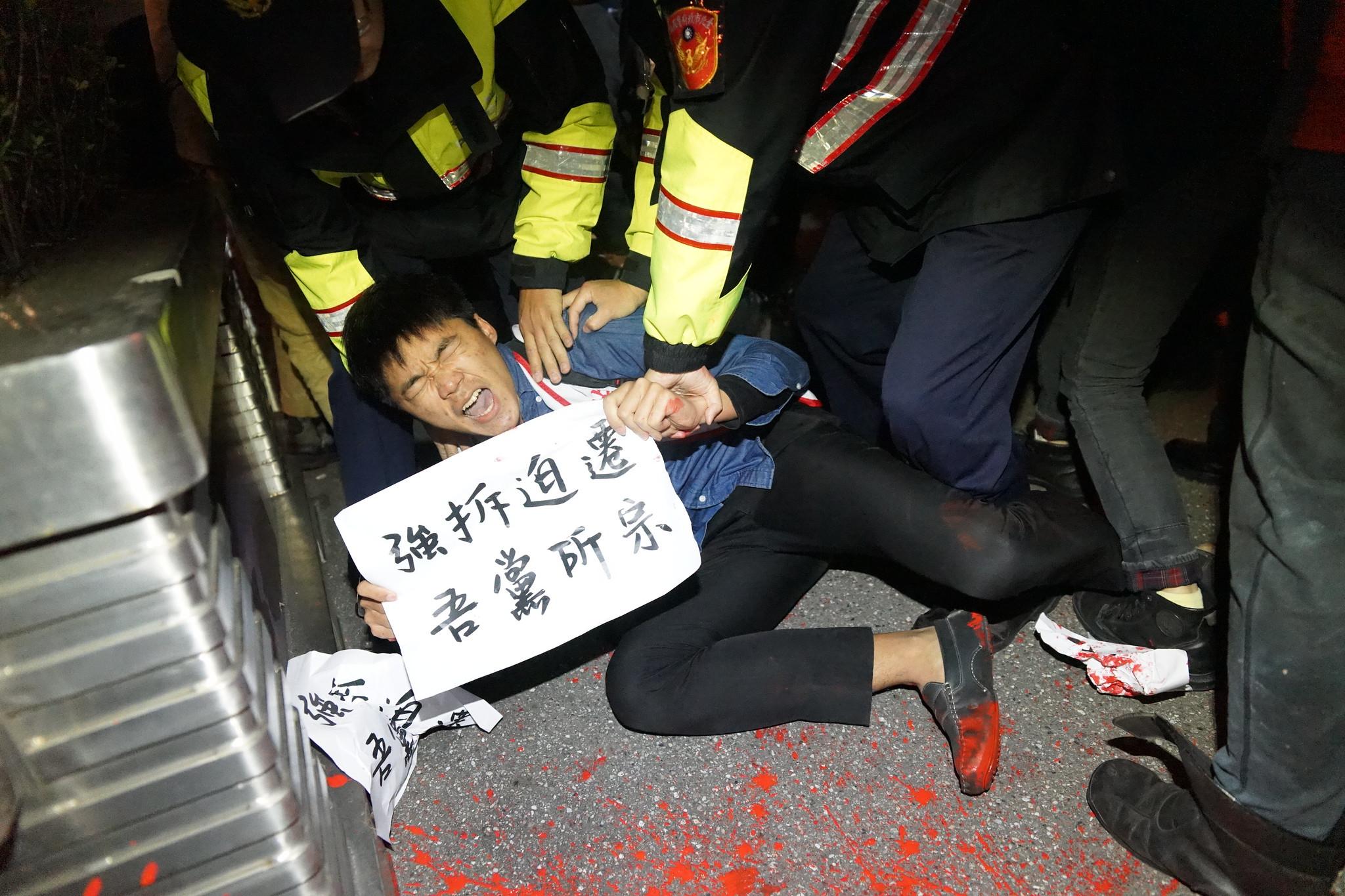 自救會成員府前潑紅漆遭警方壓制。(攝影:王顥中)