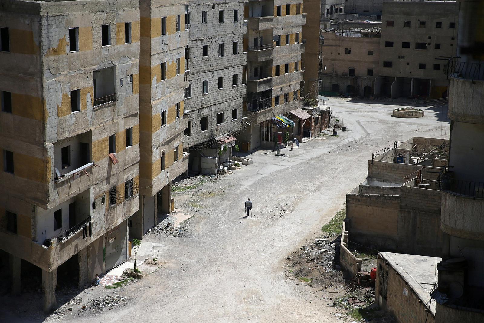 Abu Malek, uses his crutches to walk a street in Ghouta, Syria   by trust.org