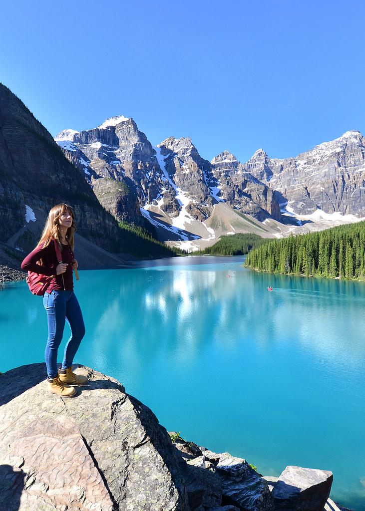 Diana subida a una roca frente al lago Moraine, de los lugares más alucinantes que ver en Canadá