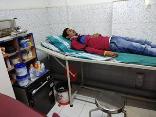 A worker on hunger strike lies in a hospital bed with a blood pressure strap on his arm