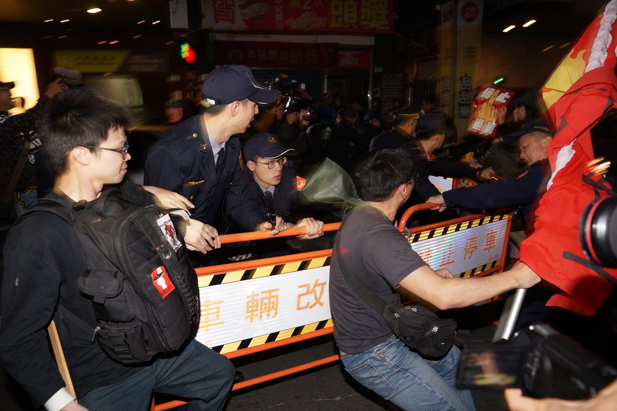 警方多次尝试设置路障阻挡队伍前进,但由于无法预测游行路线,路障总是被群众以人数优势排除而阻挡未果。(摄影:王颢中)