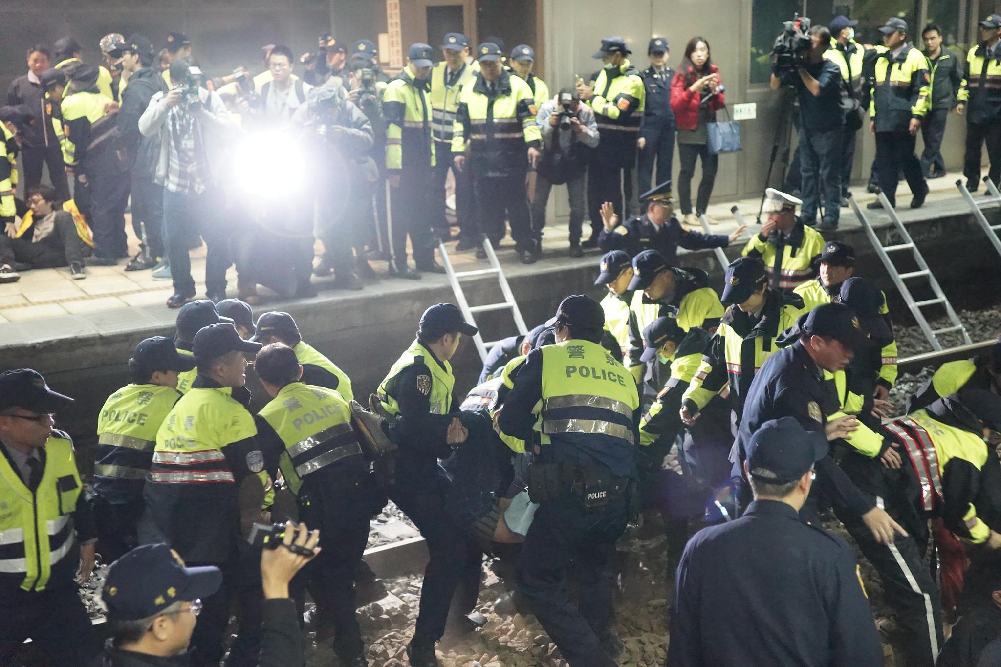 警方將第二波臥軌者抬往第四月台。(攝影:王顥中)