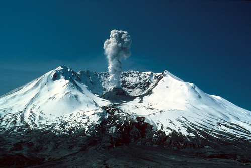 Color image shows Mount St. Helens from the north, looking in to the crater. The flanks of the volcano are covered in snow. The lower slopes are dark gray ash, riddled with eroded stream beds. A thick plume of steam and ash rises into the dark blue sky from the black dome in the center of the crater.