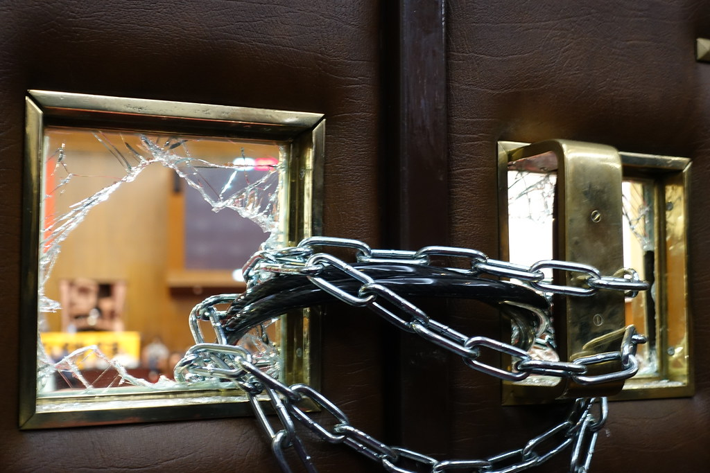 徐永明、黃國昌等人從議場門內打破大門玻璃,並用鐵鏈反鎖。(攝影:張智琦)