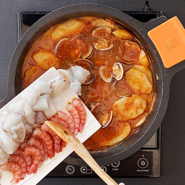 Añadiendo el pescado al suquet de peix