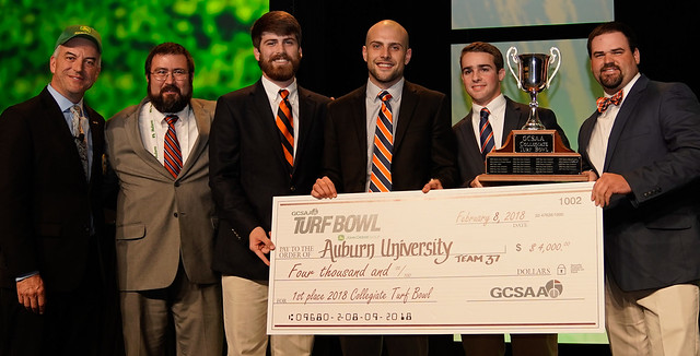 Representatives from Auburn hold a giant check after winning the 2018 Turf Bowl.