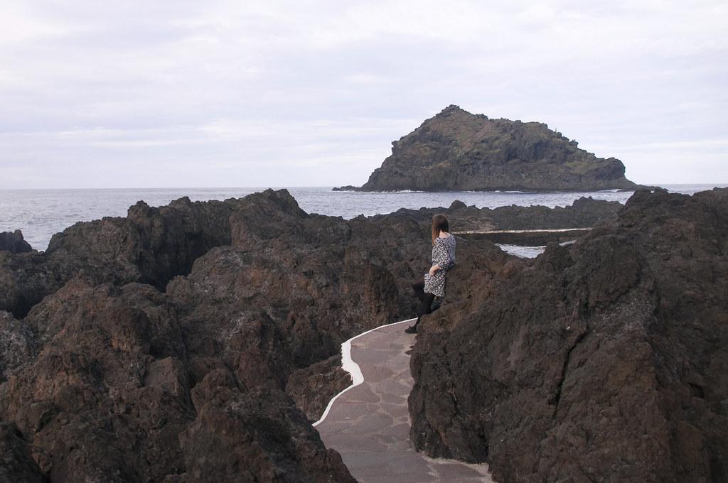 dziewczyna w sukience pomiędzy skałami w Garachico