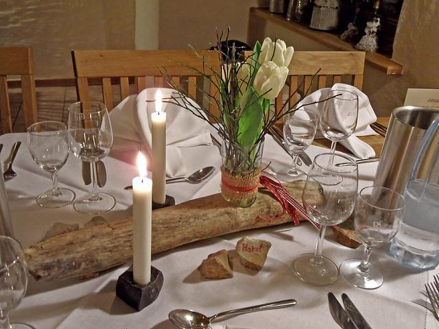 Festlich gedeckter Tisch mit Kerzen und Tulpen