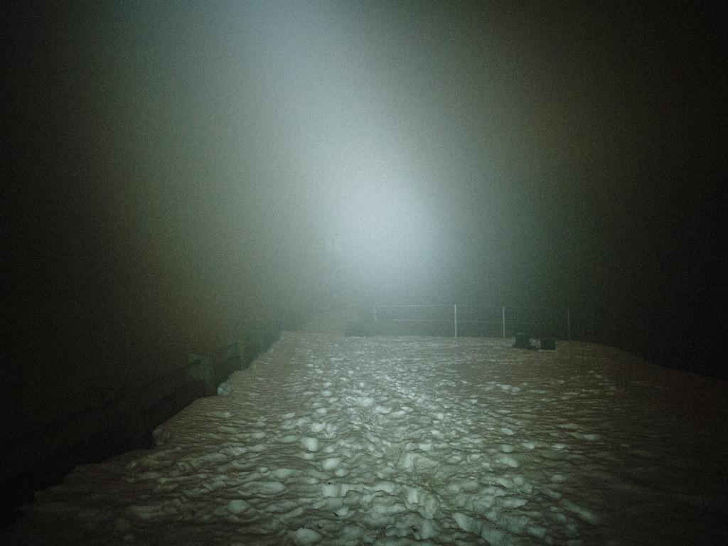 irregular footsteps in the snow, dark fog lit by headlamp