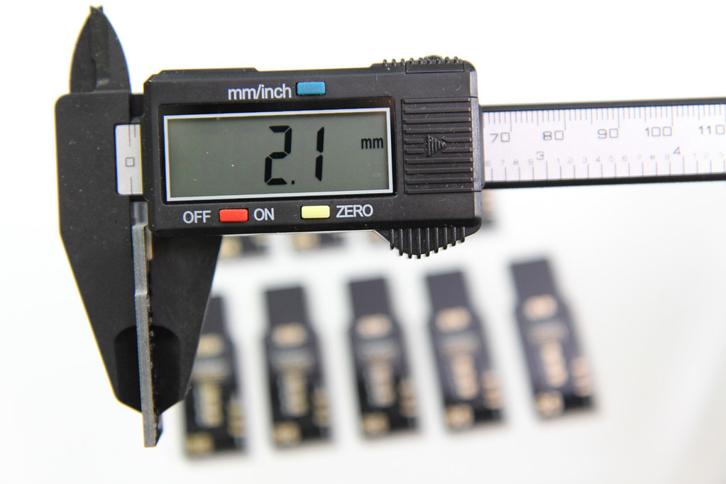 digital calipers shown measuring the board thickness