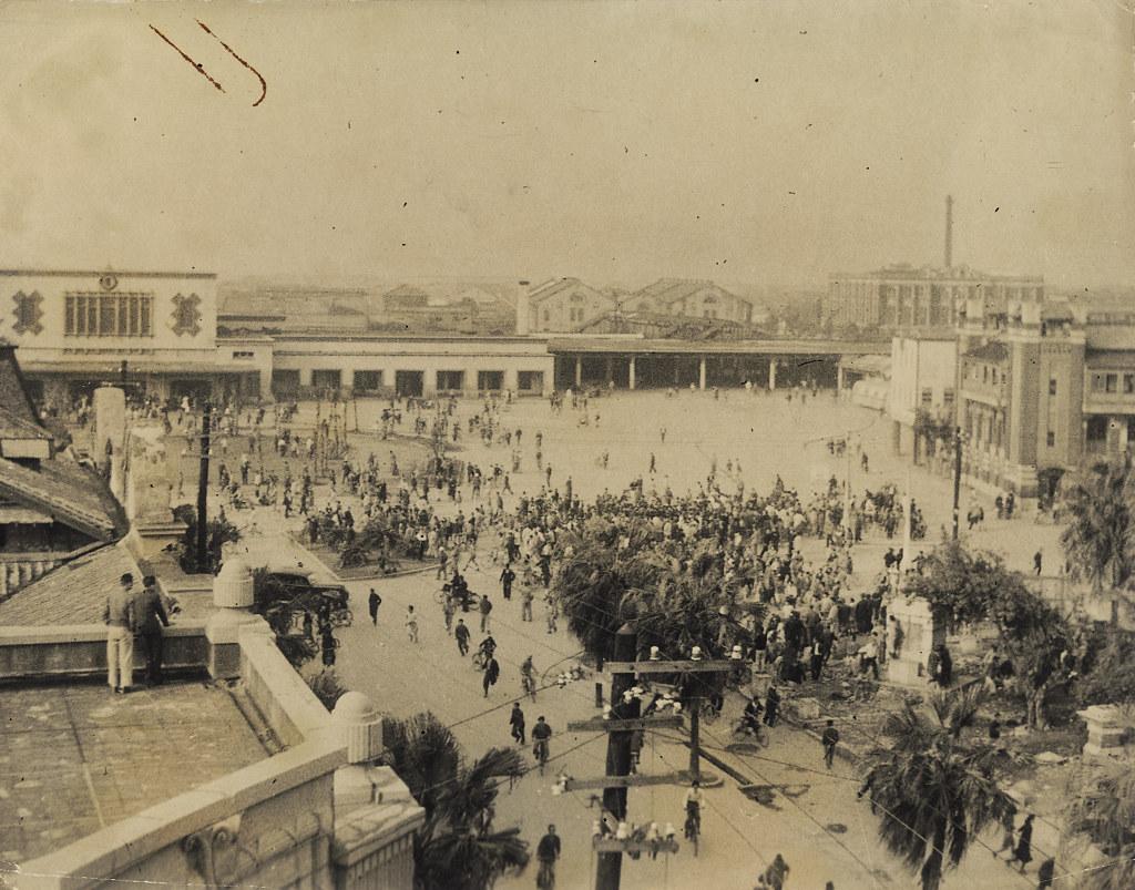 1947年2月28日中午,台北火車站前集結著準備前往行政長官公署請願的群眾,另外還有一些四處緊急通告與旁觀的民眾。(圖片來源:維基百科)