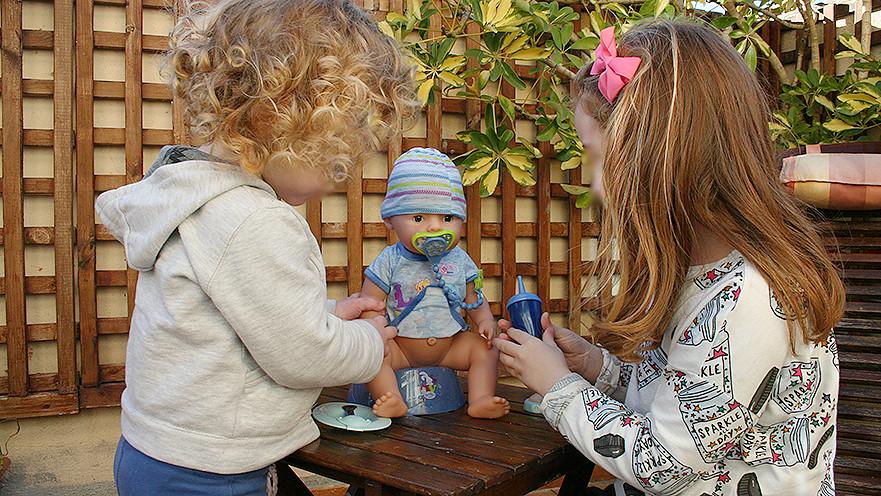 niña y niño jugando con muñeco Baby born
