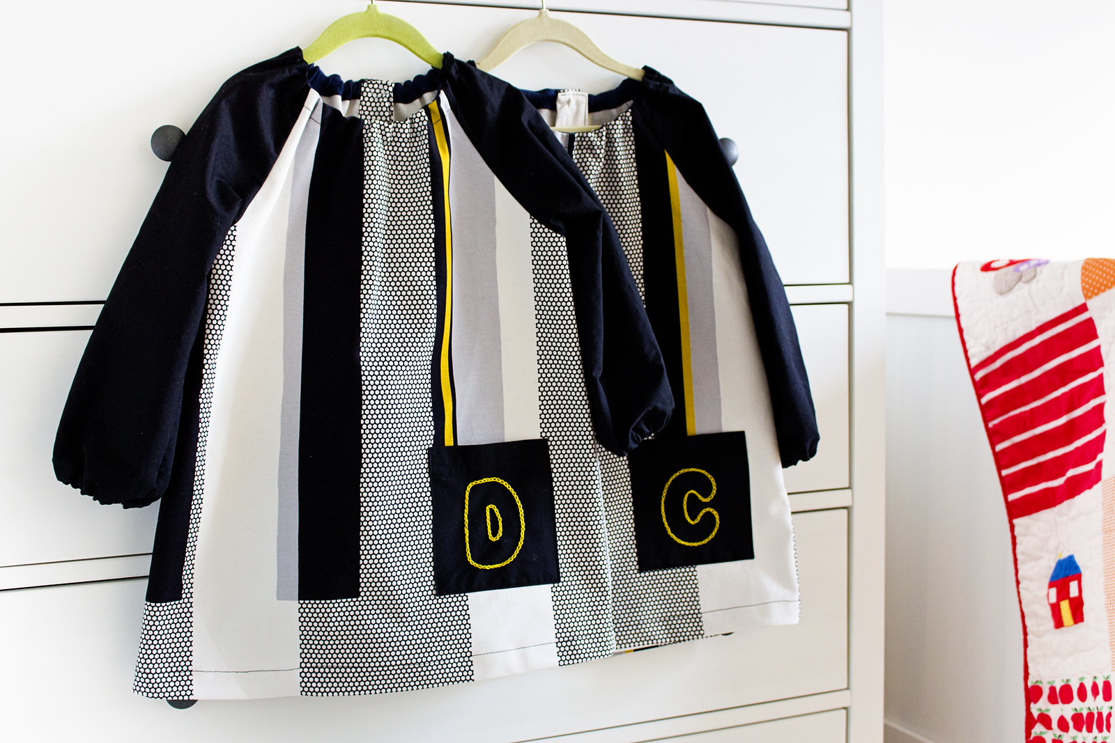Two toddler art smocks on hangers with embroidered initial detail.