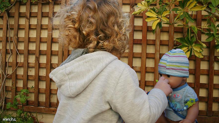 niño jugando con muñeco baby born