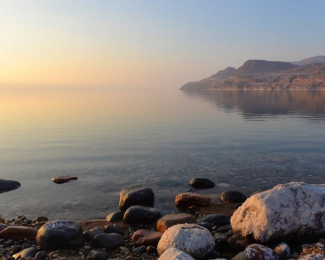 Atardecer en el Mar Muerto con rocas saladas y el agua en calma