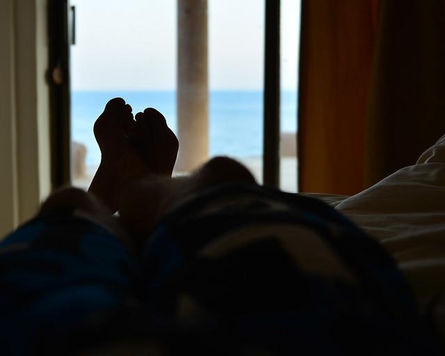 Mis pies frente a la ventana de la habitación con el mar al fondo
