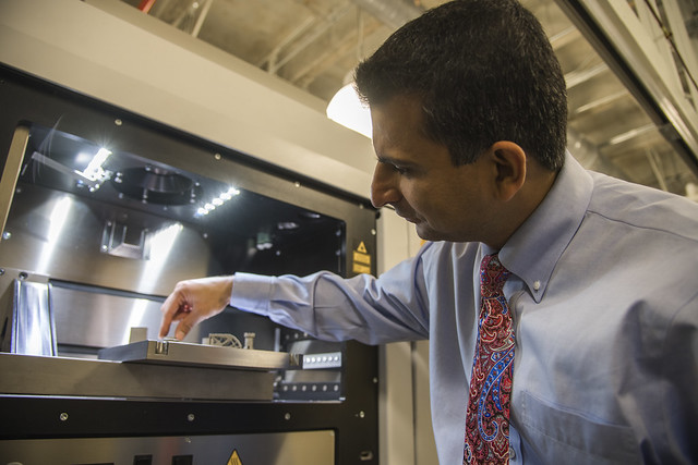 Nima Shamsaei holds a part in front of a 3-D printer.