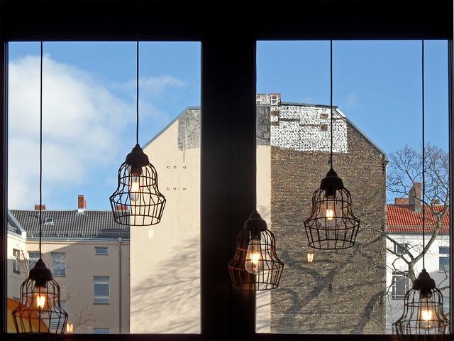 Blick durch ein Café-Fenster auf Berliner Brandmauern