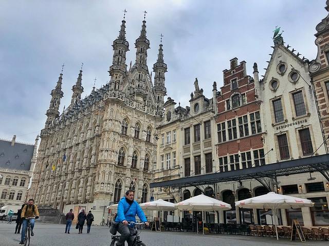 Sele montando en bicicleta en la Grote Markt de Lovaina (Flandes, Bélgica)