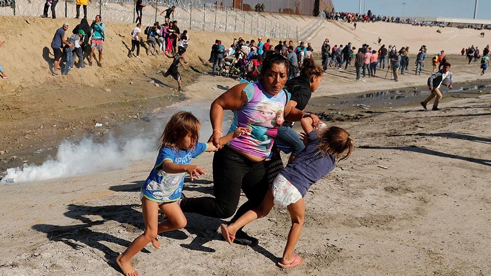一名婦人與孩童於美墨邊境前閃避催淚彈。(圖片來源:Kim Kyung-Hoon/Reuters)