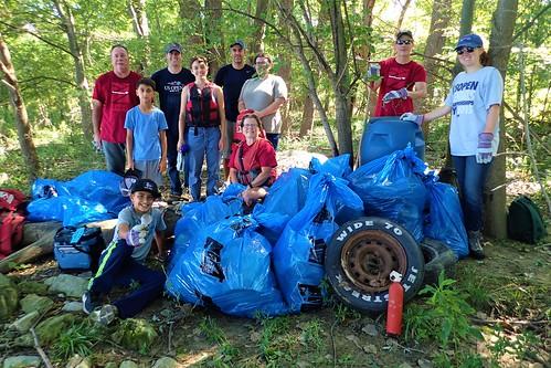 Volunteer crew flexes in front of their findings