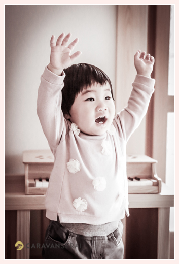 ヽ(^o^)丿をする1才の女の子