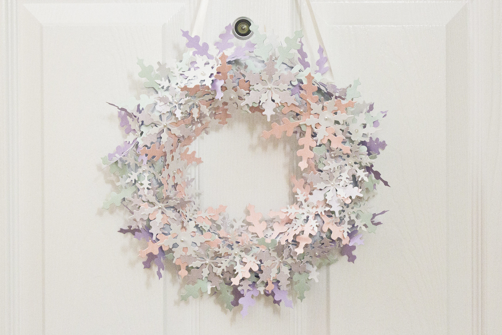 A wreath of paper snowflakes made for christmas from pastel and white