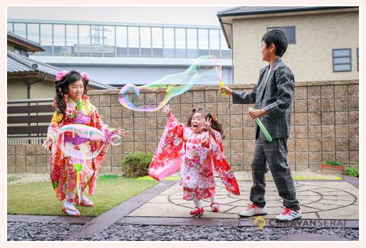 自宅の庭でシャボン玉で遊ぶ兄弟
