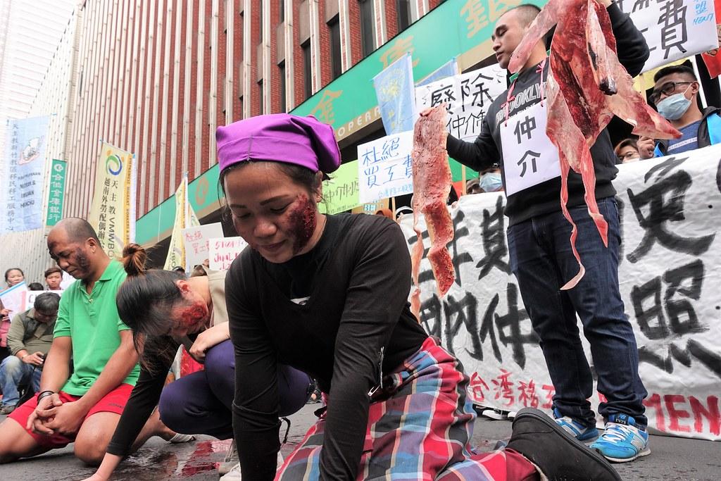 """移工团体今日到劳动部抗议被违法收取买工费,演出被仲介""""剥皮""""的行动剧。(摄影:张智琦)"""