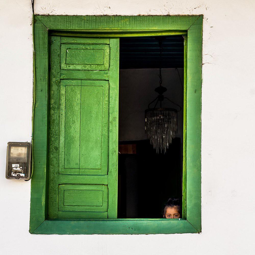 Imagen de una niña escondida en una ventana en Salento, Colombia