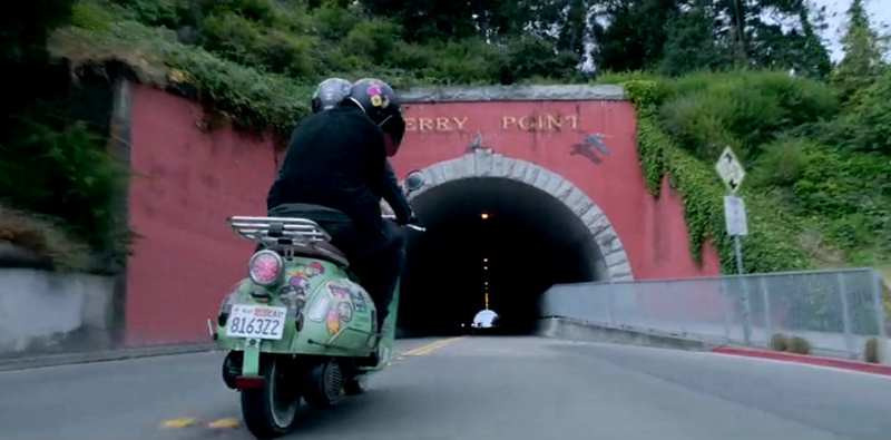 pink tunnel with two people riding a vespa bike