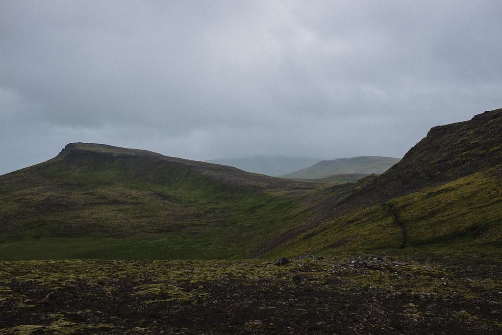 Track in barren, desolate landscape, low clouds.
